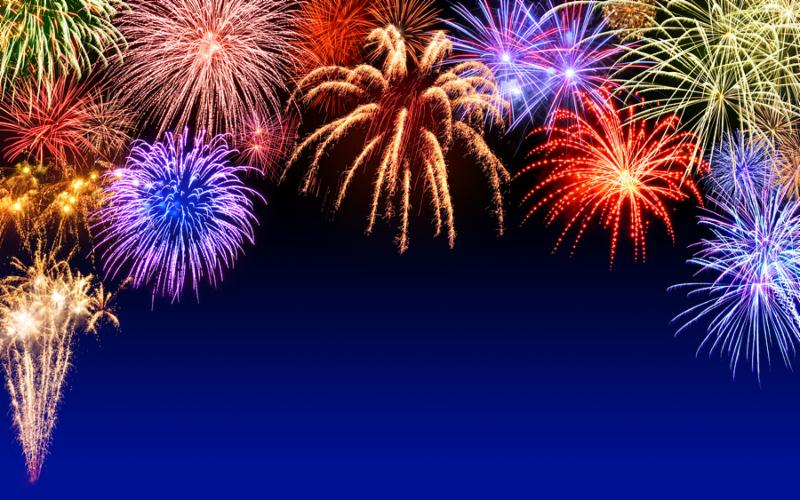 Gorgeous multi-colored fireworks display on dark blue night sky with copyspace
