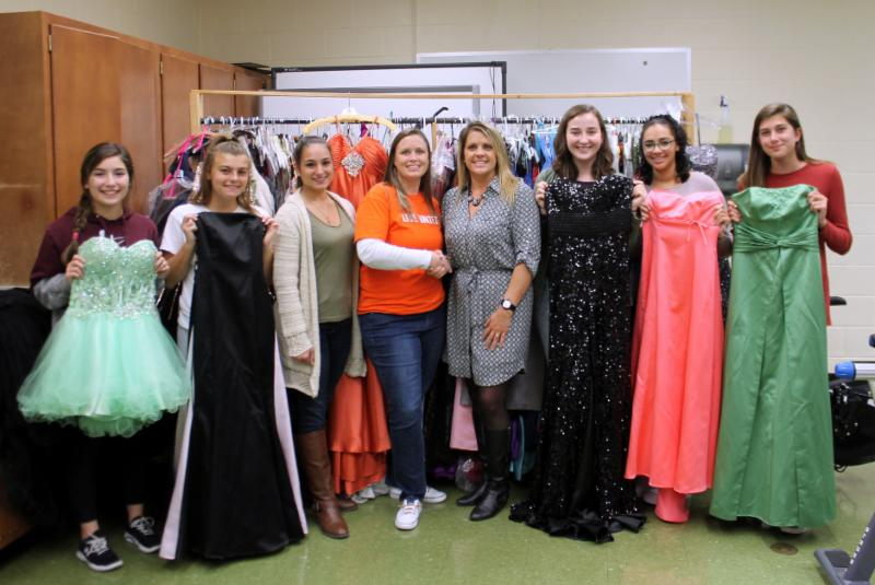 Group photo of Girls holding prom gowns donated to the United Way.