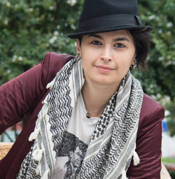 The poet and organizer Rasha Abdulhadi looks directly at the camera. They wear a black fedora and a wine colored blazer and a black and white scarf.