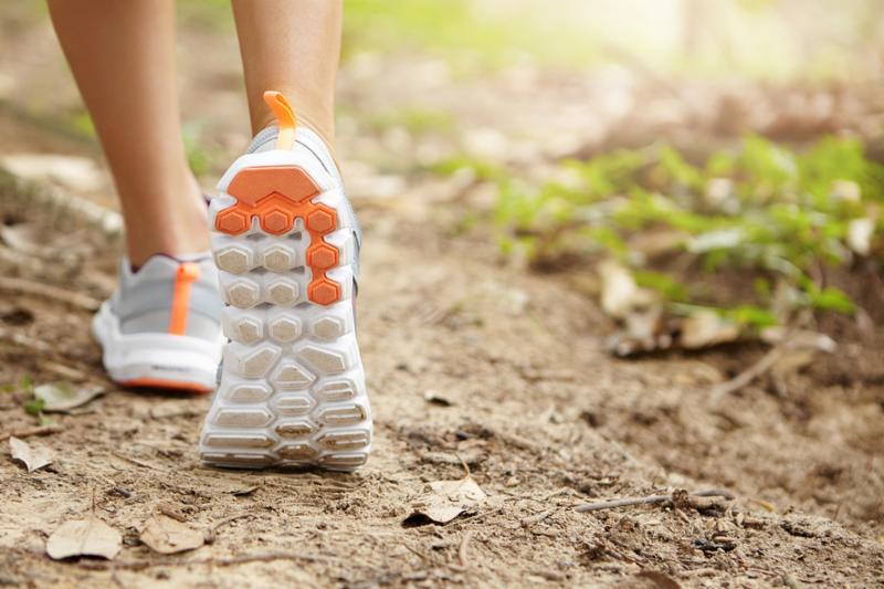 People and sports. Athletic pair of female legs in running shoes on trail. Young attractive woman jogger walking or hiking in forest or park preparing for sprint or marathon. Selective focus on sole