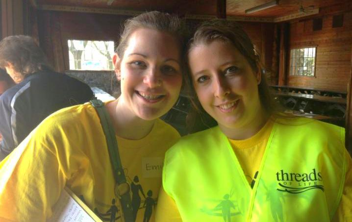 Two women in yellow t-shirts and vest smiling. One holds a clipboard.
