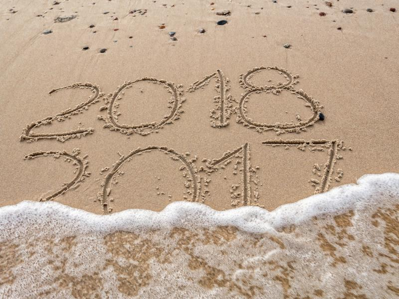 2018 and 2017 year date handwritten on the beach. New Year 2018 replacing Old Year 2017 being washed away by sea wave