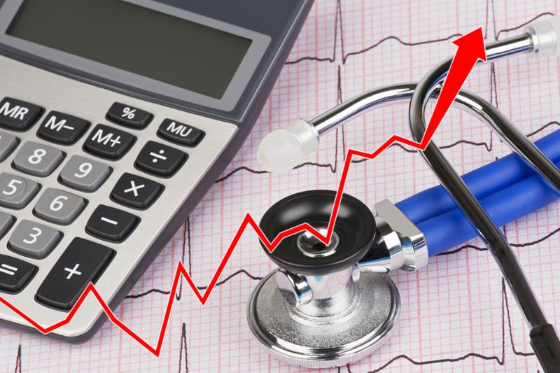 Close up of a graph with an Electrocardiograph also known as a EKG or ECG graph with a stethoscope and calculator showing the high cost of health care