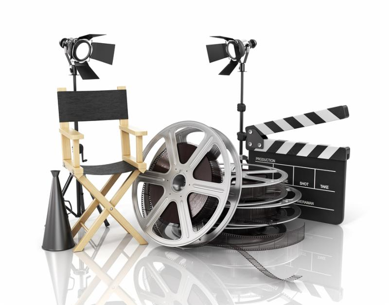 Video movie cinema concept. Light film strip reels clapperboard and director chair on the white film background.
