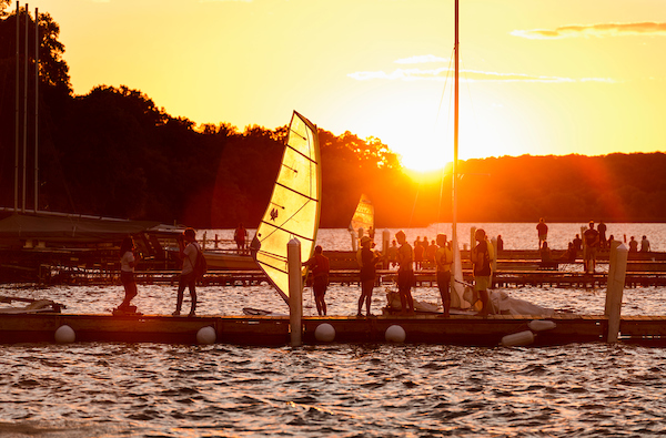 Hoofer Sailing Club members bring their windsurfing boards and sailboats in for the evening near the Memorial Union Terrace  as the summer sun sets overLake Mendota