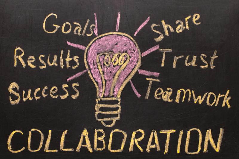Collaboration - Business concept with light bulb and text on black background