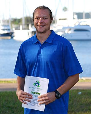 USFSP Sustainability Coordinator Brian Pullen holds a copy of the Climate Action Plan.