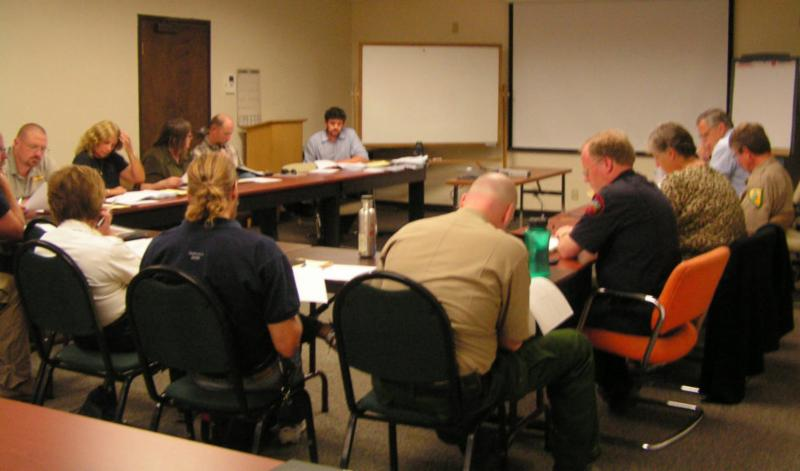 Residents and local, state, and federal firefighting agency representatives sit around a conference table during a focus group.