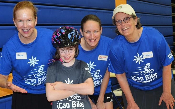 Photo of smiling girl wearing bike helmet surrounded by three smiling women, all of them wearing iCan Bike T-shirts