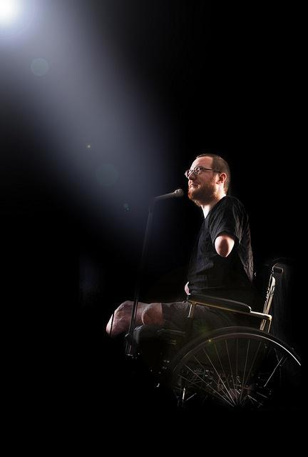 Photo of Will Lautzenheiser in his wheelchair speaking into a microphone
