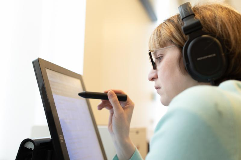 A woman wearing headphones using a stylus on a computer monitor