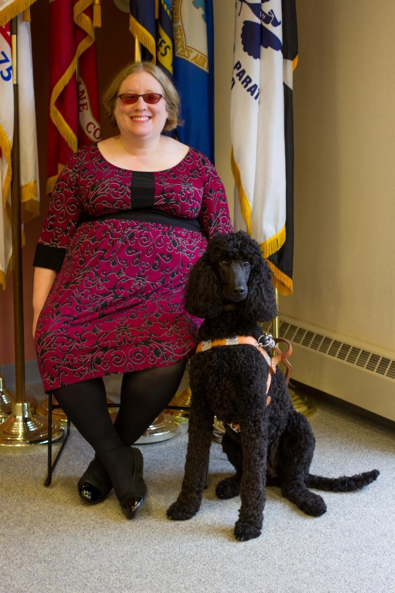 Rachel Tanenhaus seated next to her guide dog