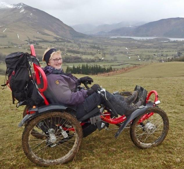 Smiling woman in all-terrain wheelchair on top of a mountain