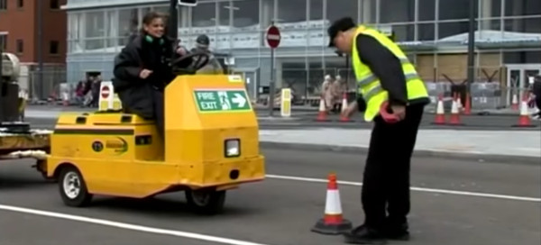 Man picks up traffic cone in front of vehicle