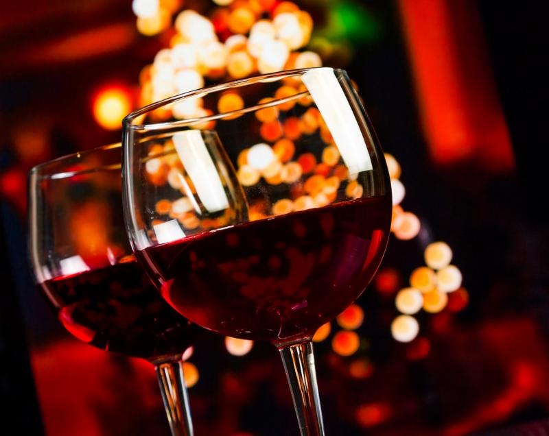 two red wine glass against christmas lights decoration background christmas atmosphere