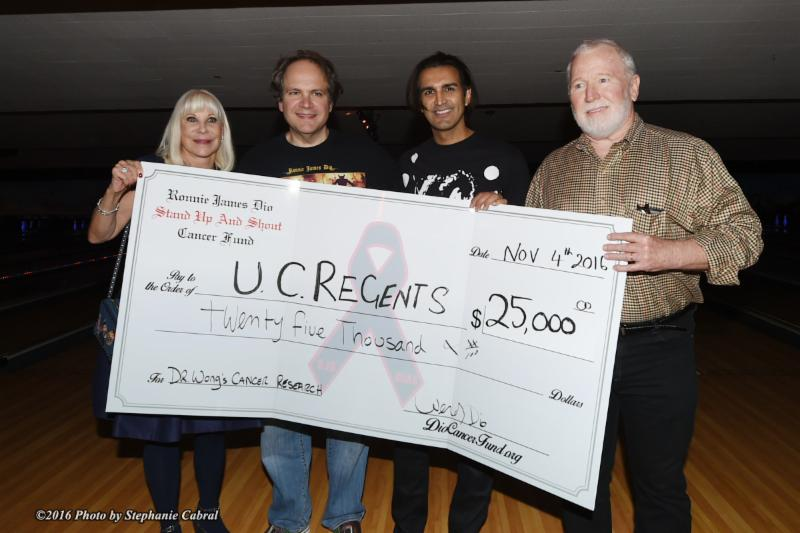 Dio Cancer Fund Founder-President Wendy Dio presents check for $25,000 to UCLA to further Dr. David Wong's development of a saliva test for cancer detection. From left: Wendy Dio, Bowl 4 Ronnie host Eddie Trunk, Dr. Sandy Kapoor, Medical Director of the Dio Cancer Fund, and David Akin, Clinical Coordinator for Dr. Wong's research project at the UCLA School of Dentistry (photo by Stephanie Cabral)