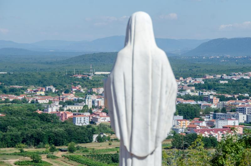 statue overlooking village