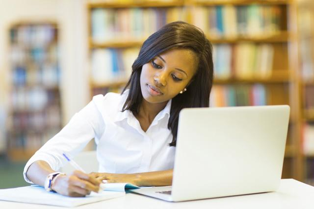 high school student studying in library with notebook and laptop