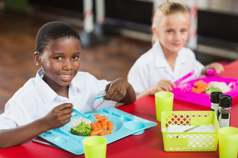 two children eating school lunch