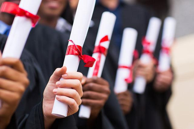 several rolled up diplomas in students_ hands
