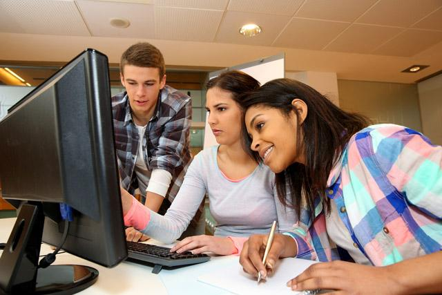three students using a computer together