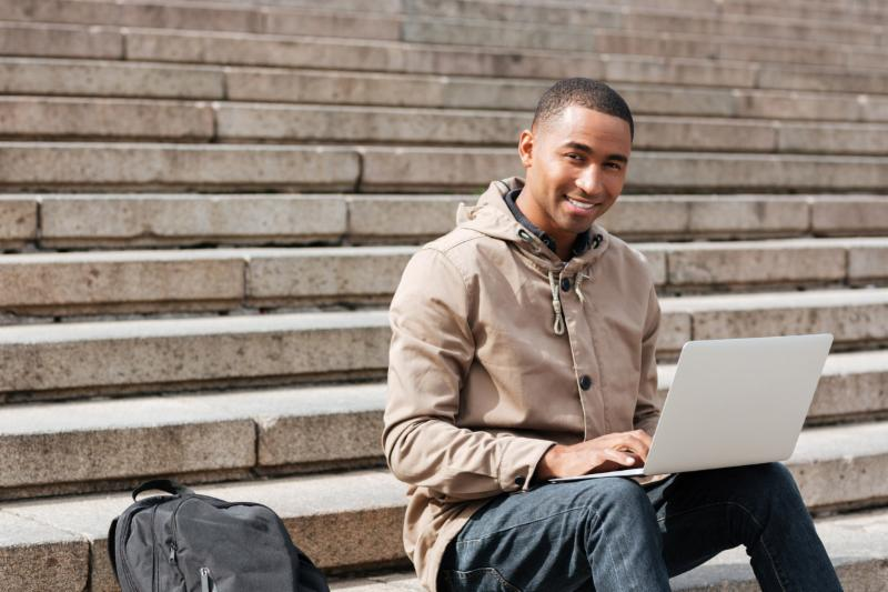 student sitting outside on steps with laptop and backpack