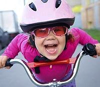 kid in pink jacket riding bike