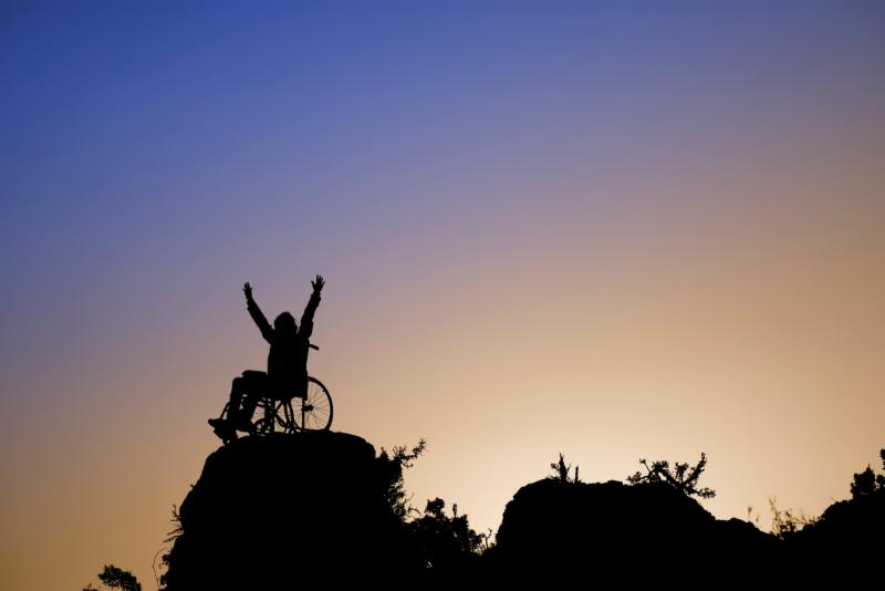 silhouette of person in wheelchair atop mountain