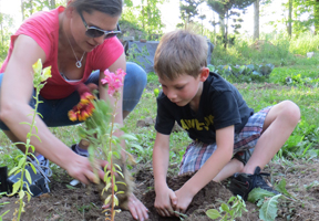 Photo of adult and child planting garden by Katrina Farmer
