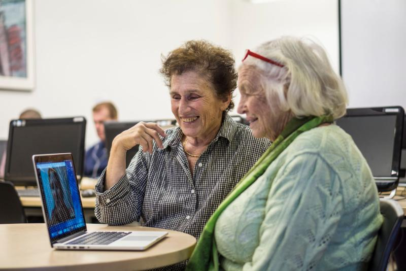 two seniors looking at a lap top