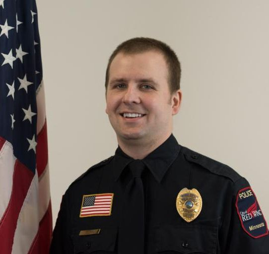 Photo of Officer Dahl next to the American flag