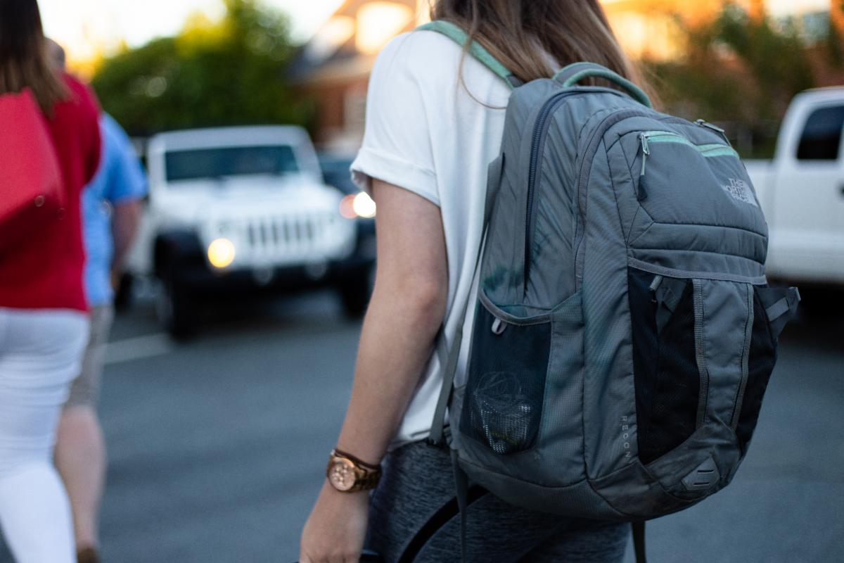 Image of a child wearing a grey backpack walking