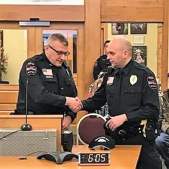 Photo of Police Chief Pohlman shaking the hand of Officer Huberty in the City Hall Council Chambers