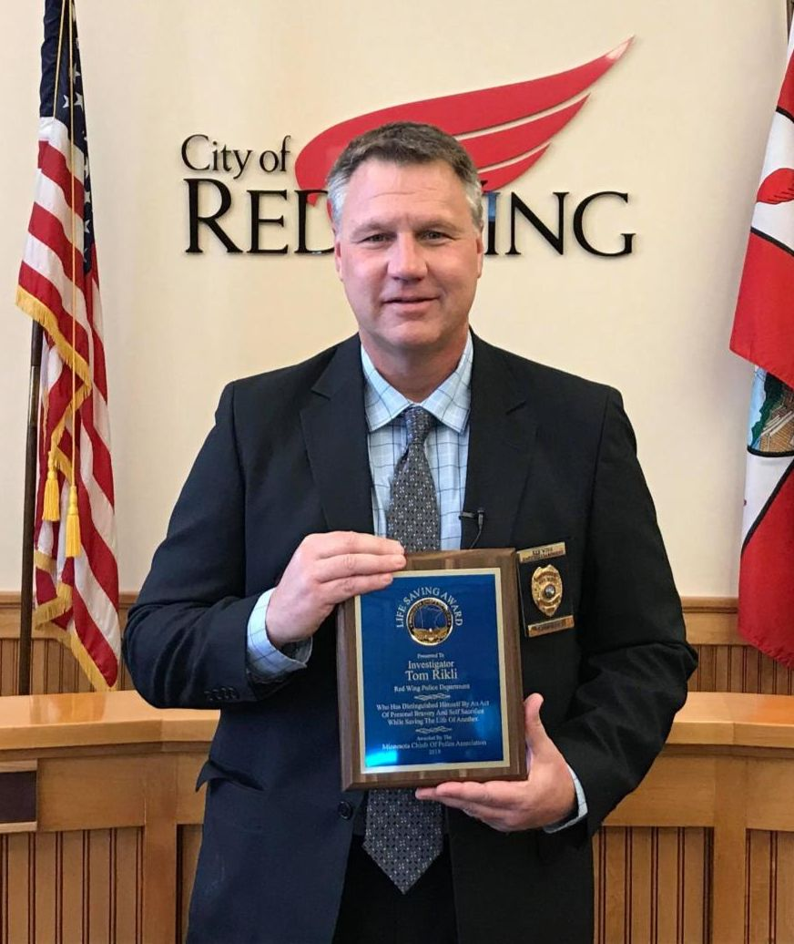 Photo of Tom Rikli standing in Council Chambers holding livesaving award