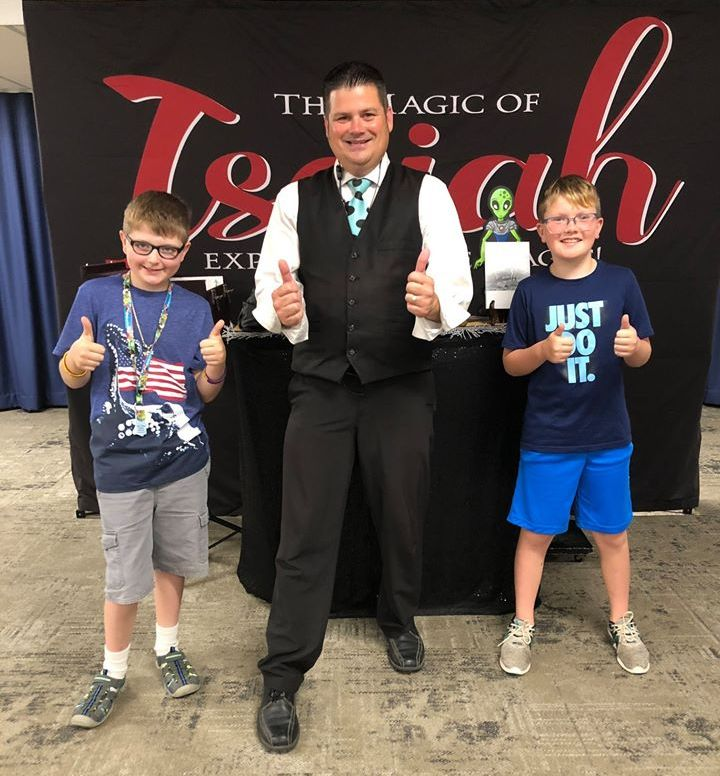 Image of Isaiah the magician giving the thumbs up with two boys