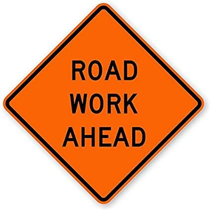 Orange diamond shaped sign stating Road Work Ahead
