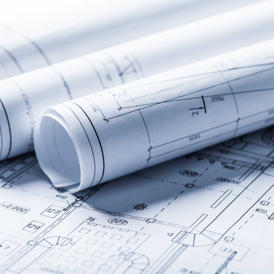 Photo of rolled blueprints laying on top of a flat blueprint