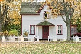 Photo of a white house with red trimming and white picket fence in the fall