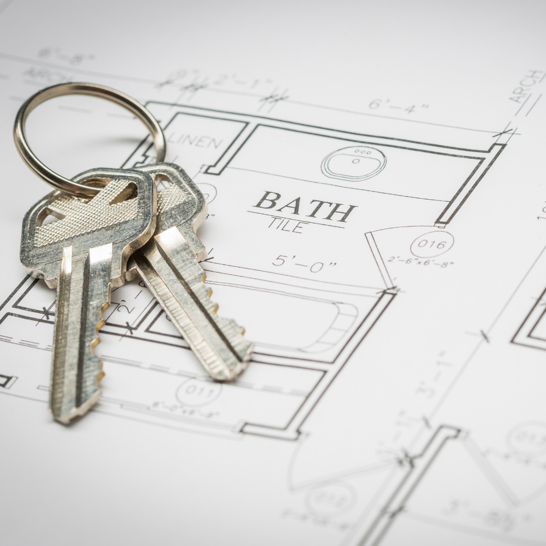 Photo of a pair of keys laying on a housing blueprint in white