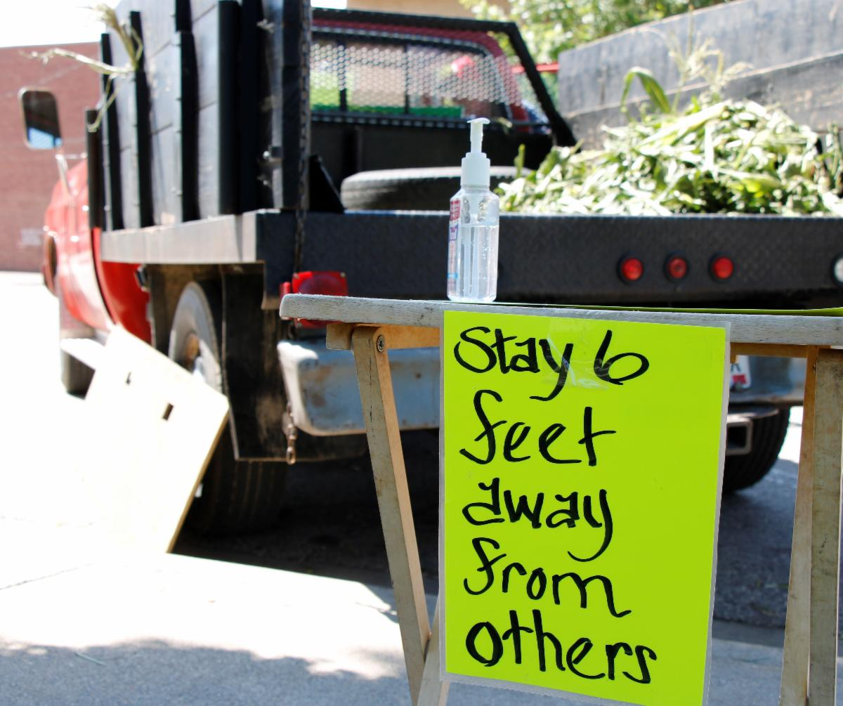 Sign advising social distancing in front of a sweet corn vendor's truck