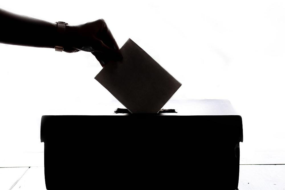 Image of a hand dropping an envelope into a box backlit against a white background