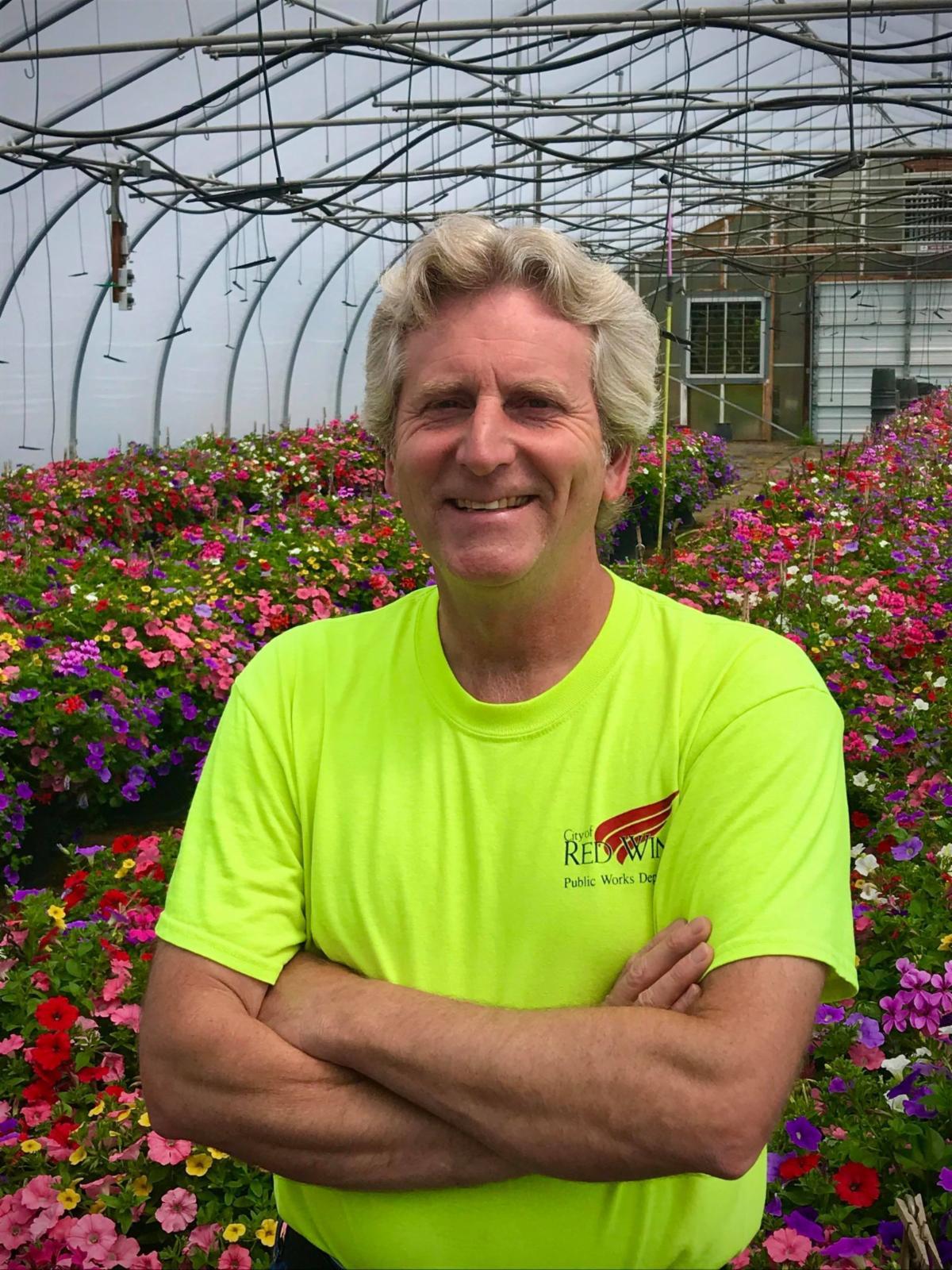 Photo of Brian Biwer standing amongst flower baskets