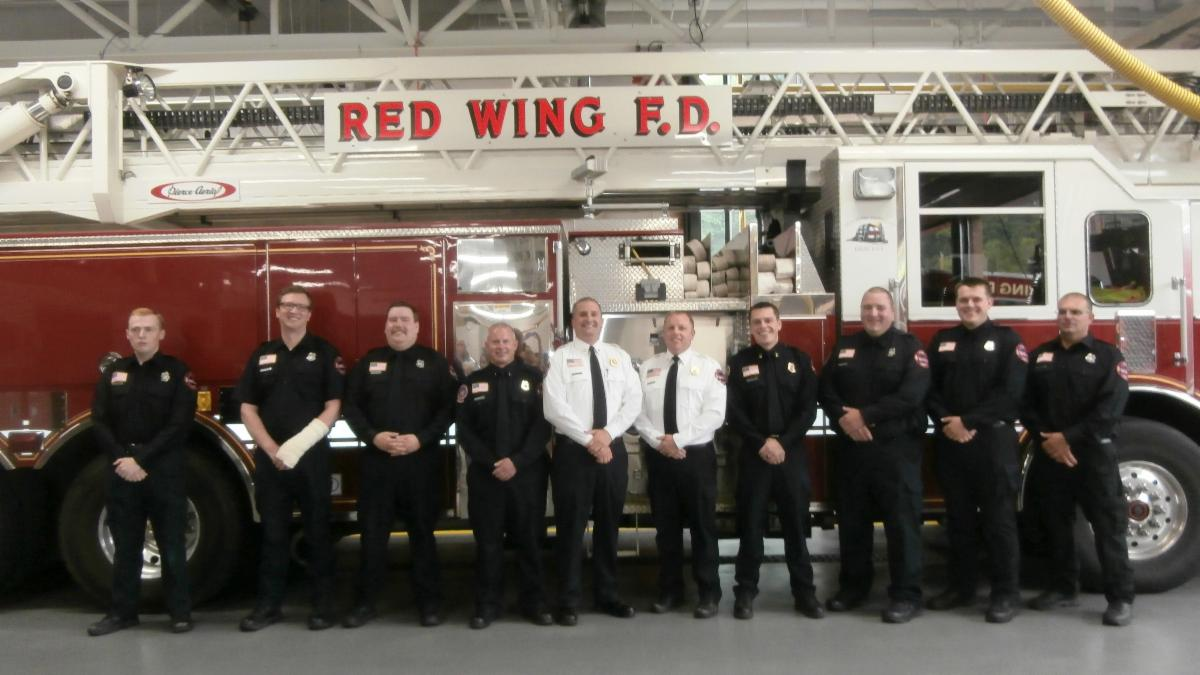 Group photo of firefighters standing in front of a ladder truck.