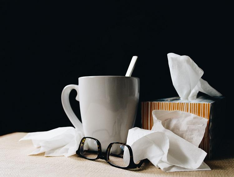 Photo of gray mug glasses and tissues in front of a black background