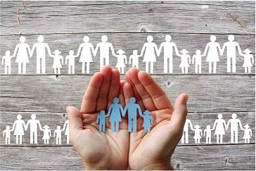 Image of hands holding paper cut-outs of people in front of a background of white paper cut-outs