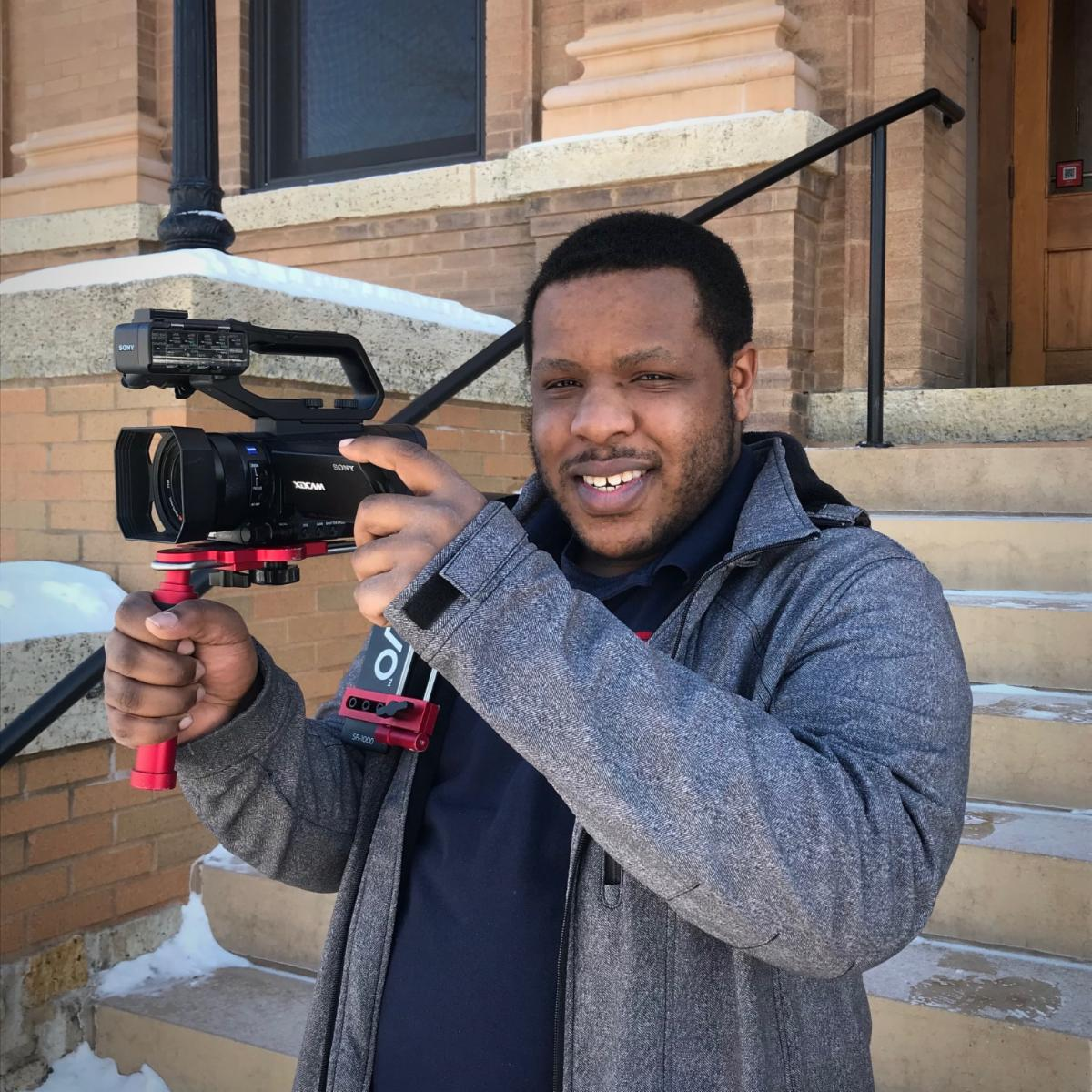 Photo of Macio outside City Hall holding a camera
