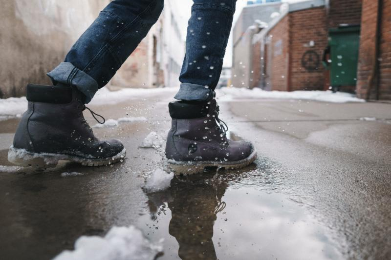 Image of a person wearing jeans and black boots standing in a snowy puddle