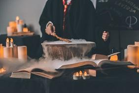 Photo of someone wearing school robes standing over a table full of candles books and bubbling bowl