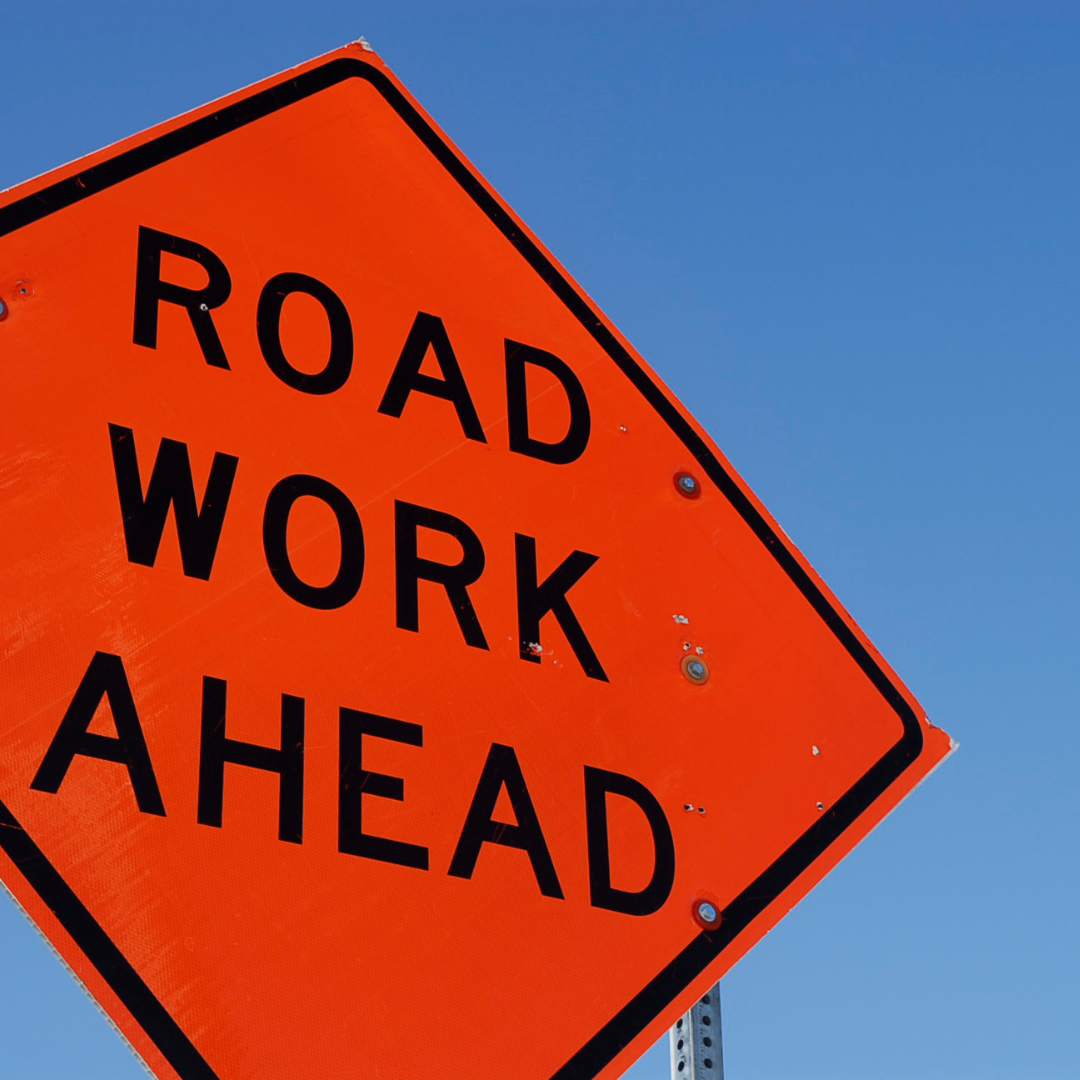 Close up photo of a yellow Road Work Ahead sign shot from below