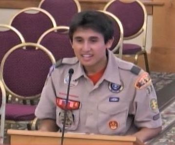 Eagle Scout in uniform presenting at a podium